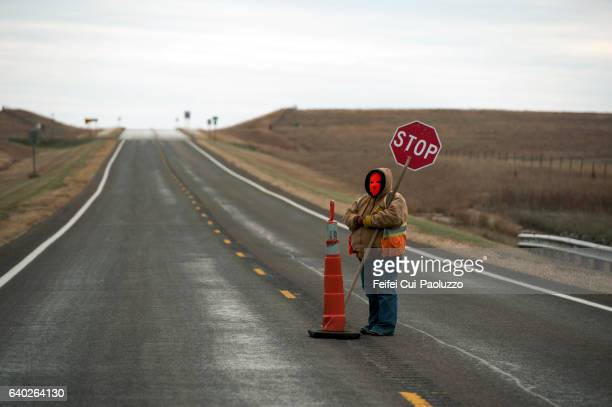 one person holding a stop road sign near marion of kansas state in usa - kansas state v kansas stock pictures, royalty-free photos & images