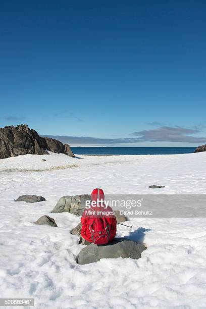 One person in an orange jacket sitting taking in the landscape on an Antarctic island.