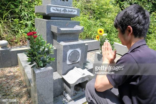 墓石の前で一人