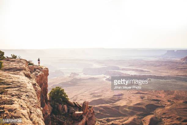 one person overlooking canyonlands national park in utah during sunset - utah stock pictures, royalty-free photos & images