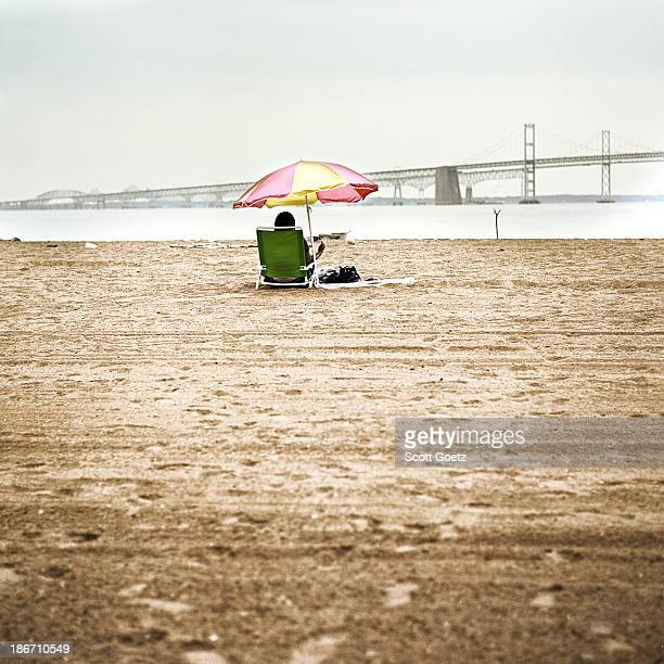 One person sitting at beach under an umbrella, with a large bridge and water in the background. Color image, with muted colors.