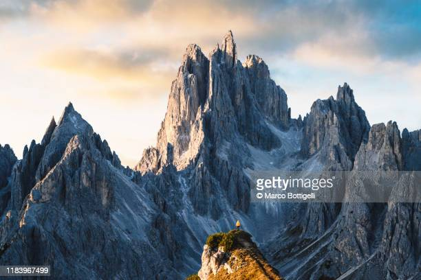 one person standing in front of sharp dolomites peaks, italy - mountain stock pictures, royalty-free photos & images