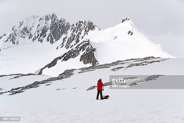One person standing on the ice in front of a snow-covered mountain.