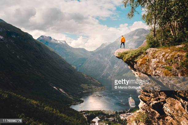 one person standing on top of a cliff over geiranger, norway - buitensport stockfoto's en -beelden