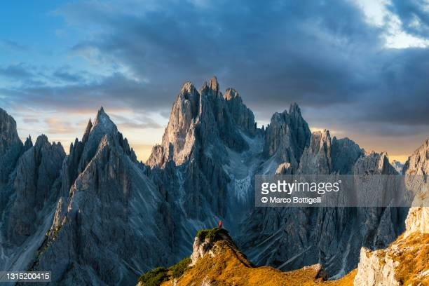 one person standing on top of a mountain ridge in the dolomites, italy - rock formation stock pictures, royalty-free photos & images