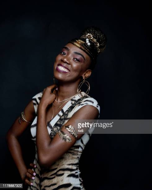 one person / waist up of 20-29 years old adult beautiful black hair african ethnicity / african-american ethnicity female / young women standing in front of black background wearing dress who is smiling / happy / cheerful / laughing / cool attitude - 25 29 years stock pictures, royalty-free photos & images