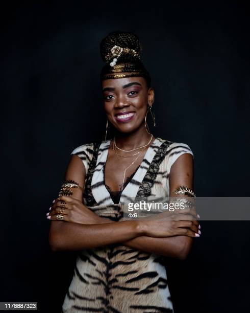 one person / waist up of 20-29 years old adult beautiful black hair african ethnicity / african-american ethnicity female / young women standing in front of black background wearing dress who is smiling / happy / cheerful / laughing / confidence - 25 29 years stock pictures, royalty-free photos & images