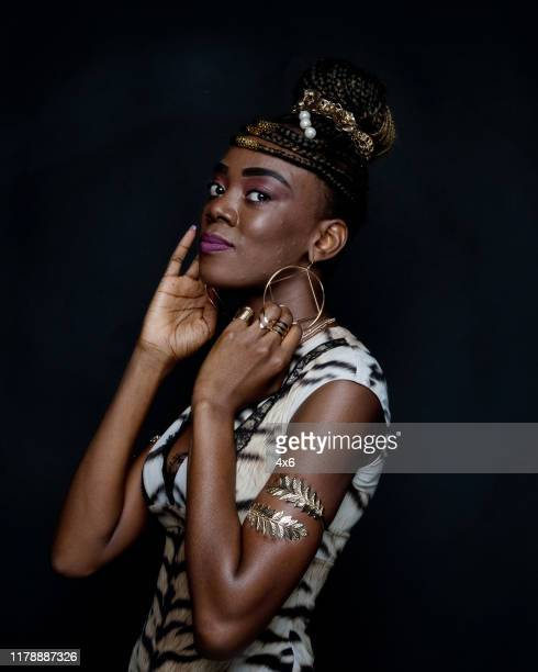 one person / waist up of 20-29 years old adult beautiful black hair african ethnicity / african-american ethnicity female / young women standing in front of black background wearing dress who is serious / confidence / concentration / cool attitude - 25 29 years stock pictures, royalty-free photos & images