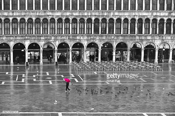 One person with a red umbrella crossing the St Mark's Square by a rainy day in winter in Venice, Italy.