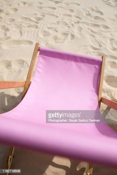 One pink lounge chair on sand in summer