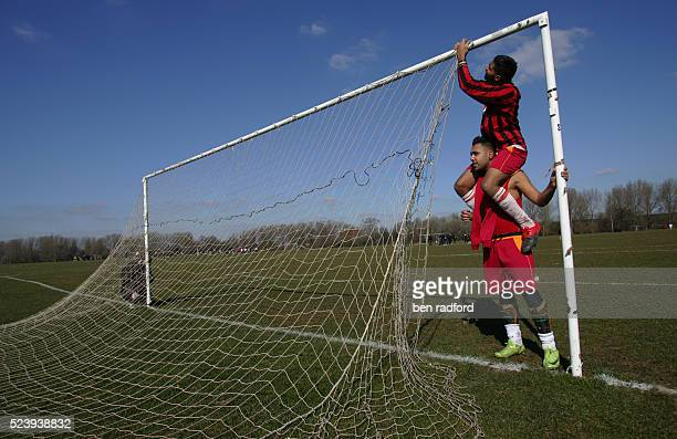 One player sits on another's shoulders to help with the process of attaching and removing the goal net during Sunday morning football at Hackney...