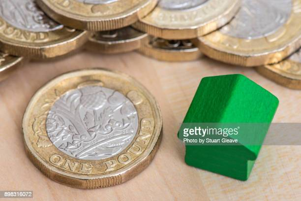 """""""one pound"""" (£1 coin) and positive (green) house - house rental stock photos and pictures"""