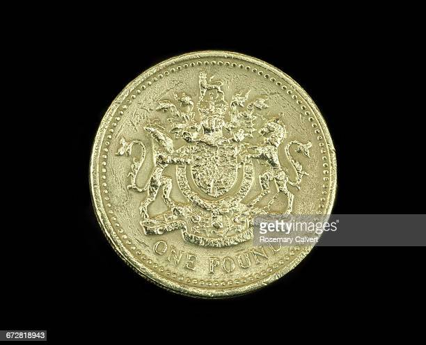 One pound coin in close-up on black.