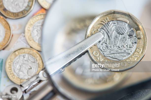 One pound coin under magnifying glass