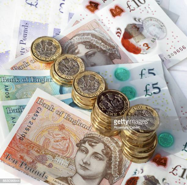 one pound coins in ordered stacks on pound notes. - british currency stock pictures, royalty-free photos & images
