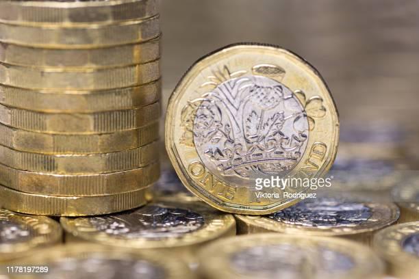 one pound coins - british currency stock pictures, royalty-free photos & images