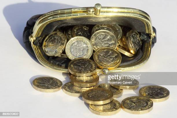 One pound coins tumbling out of purse filled to bursting.
