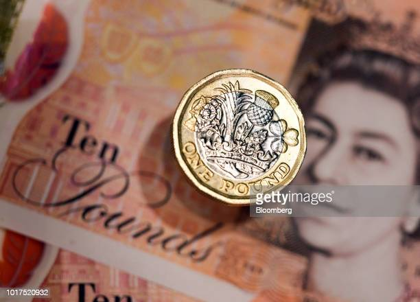 A one pound sterling coin and 10pound banknote sit in this arranged photograph in London UK on Wednesday Aug 15 2018 The pound's weakness is turning...