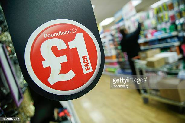 A one pound sterling sign hangs near shelves at a Poundland Group Plc store in Leigh UK on Thursday Feb 4 2016 UK like for like sales at midmarket...