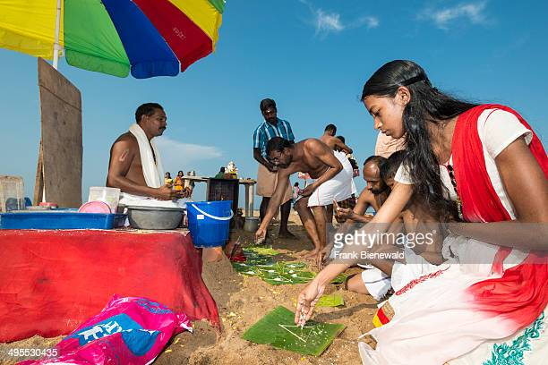 One priest is offering the Veli Tarpanam Pooja a farewell ritual for passed away family members to a pilgrim family on the beach