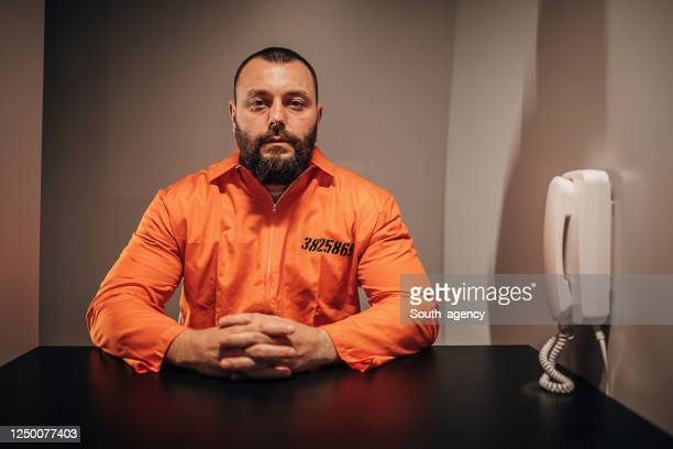 one prisoner sitting in prison visiting room - confession law stock pictures, royalty-free photos & images
