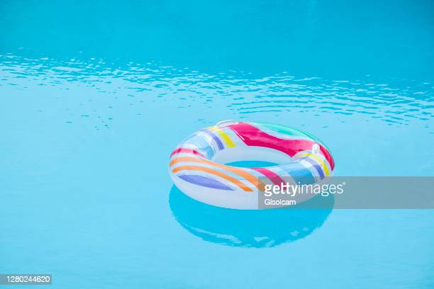 one rainbow inflatable tube float in swimming pool - swimming pool stock pictures, royalty-free photos & images