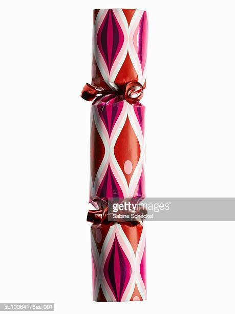 one red and pink party cracker on white background - クリスマスクラッカー ストックフォトと画像