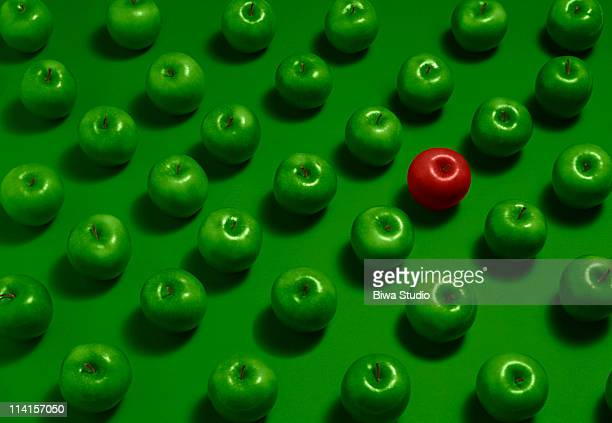 one red apple with many green apples - individualität stock-fotos und bilder