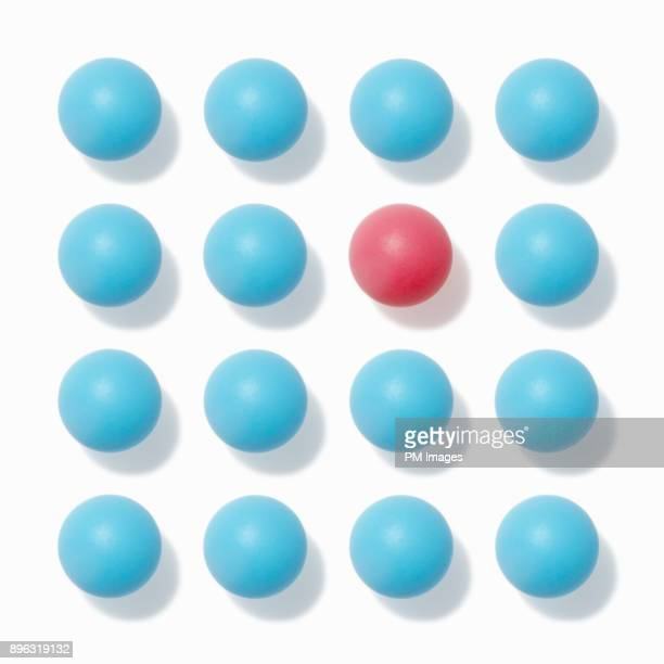 one red ball among many blue balls - sphere stock pictures, royalty-free photos & images