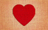 one red burlap heart brown background