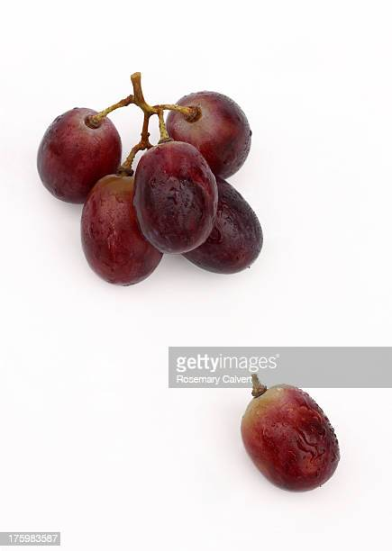 One red grape escapes from the bunch.