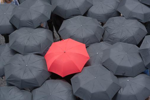 One red umbrella at center of multiple black umbrellas - gettyimageskorea