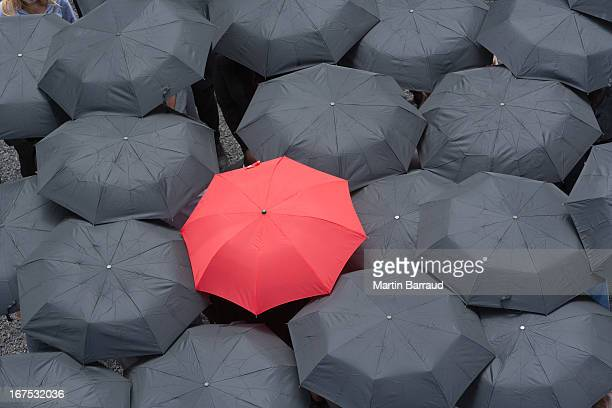 one red umbrella at center of multiple black umbrellas - individuality stock pictures, royalty-free photos & images