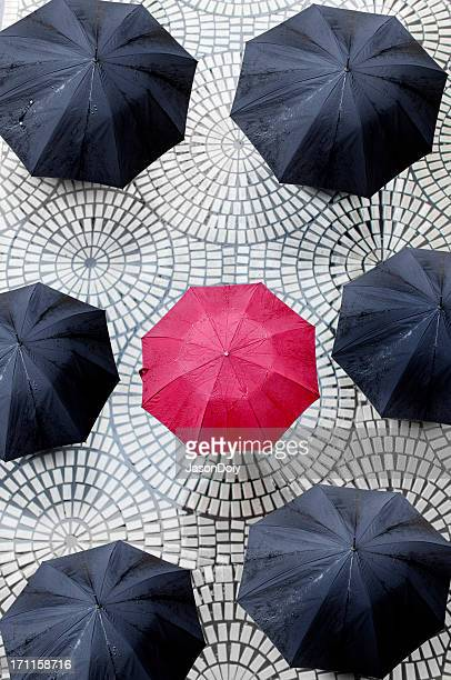 One red umbrella encircled by black umbrellas