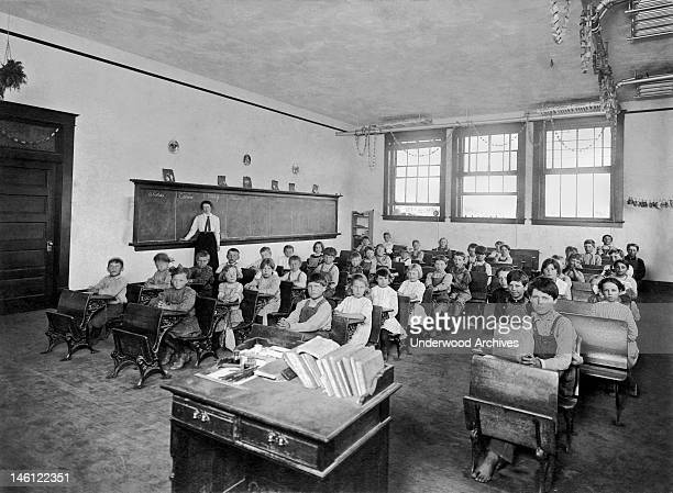 A one room school house with children of all ages late 19th or early 20th century