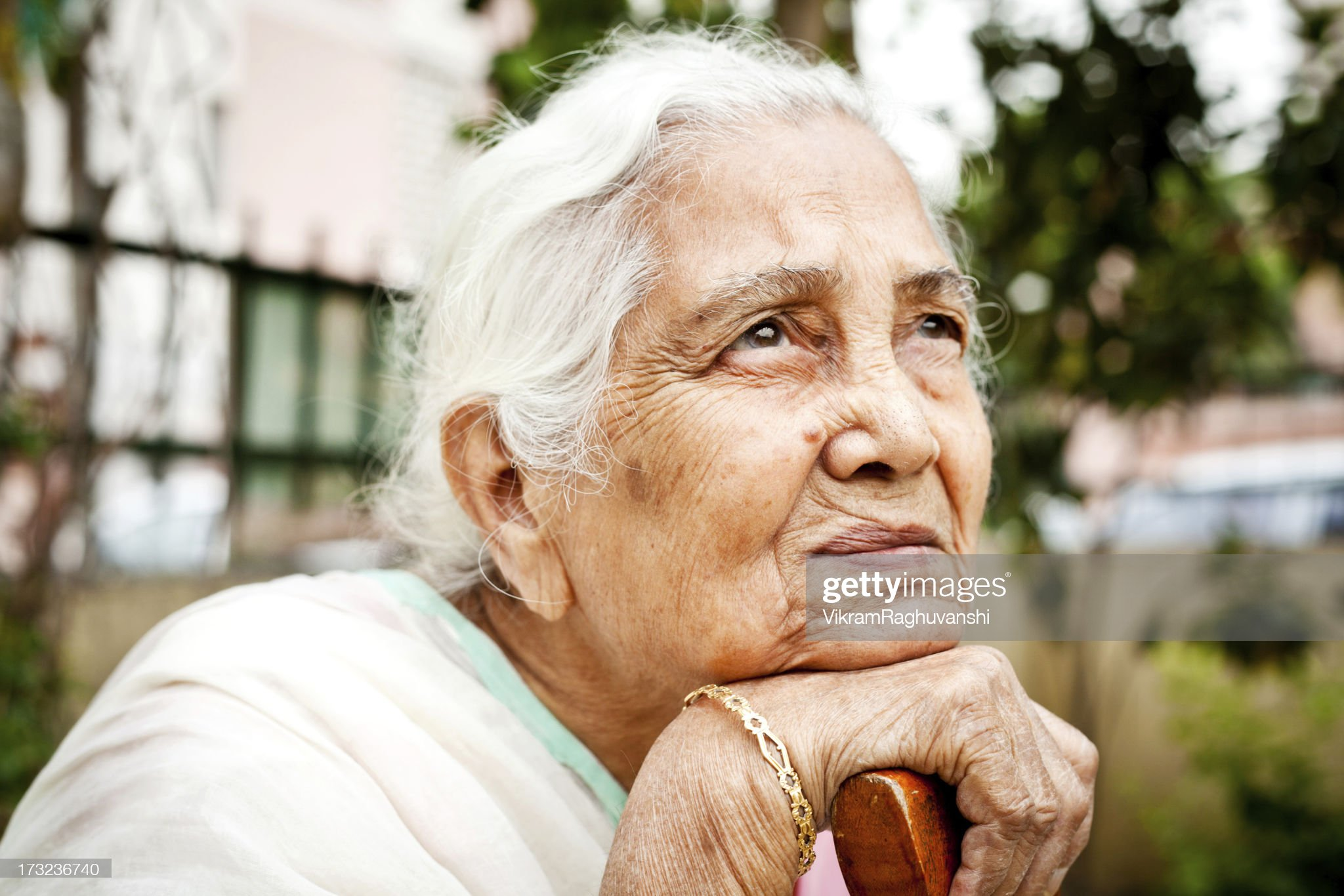 One sad pensive senior Indian woman looking up : Stock Photo