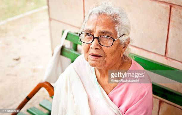 One sad pensive senior Indian woman sitting outdoors