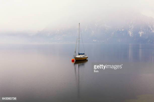 One sailboat on a lake in the mountains