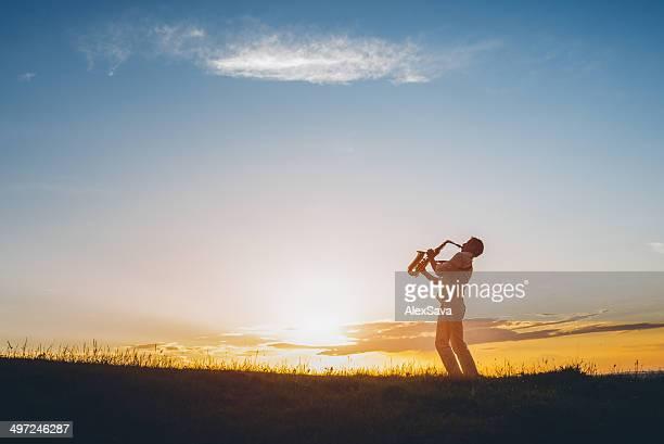 Un Sassofonista riproduzione di musica all'aperto al tramonto