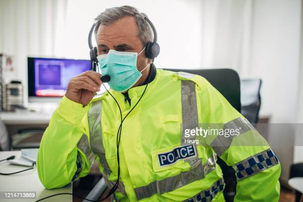 one senior british police officer with protective mask in the office - police stock pictures, royalty-free photos & images