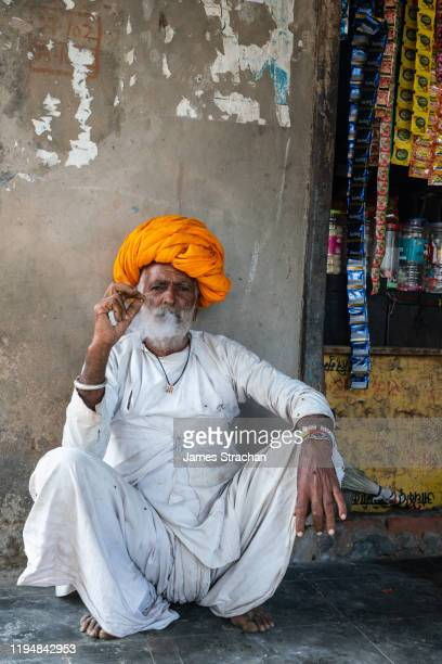 one senior male gujar villager in traditional white tunic and bright orange turban smoks a bidi (thin cigarette/small cigar) in the shade, pushkar, rajasthan, india (model release) - james strachan stock pictures, royalty-free photos & images