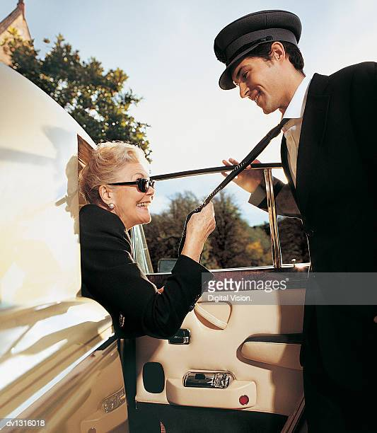 one senior woman alighting from a limousine holding the tie of her chauffeur - cougar woman fotografías e imágenes de stock