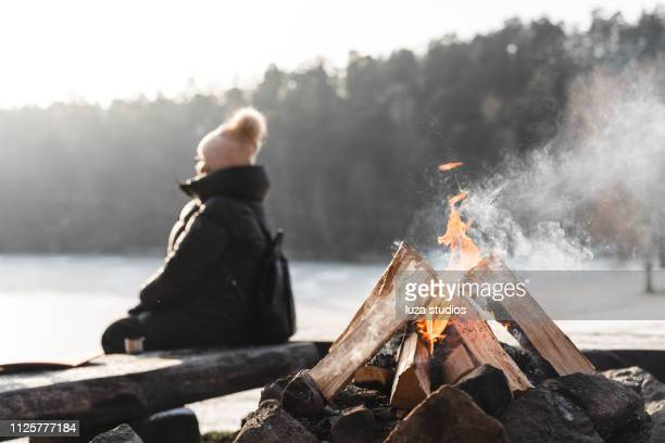 one senior woman by a campfire in winter - winter stock pictures, royalty-free photos & images
