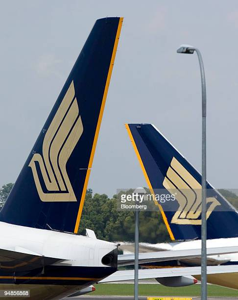 One Singapore Airlines Ltd jet moves past another parked at a gate at Changi airport in Singapore on Thursday Nov 6 2008 Singapore Airlines Ltd...