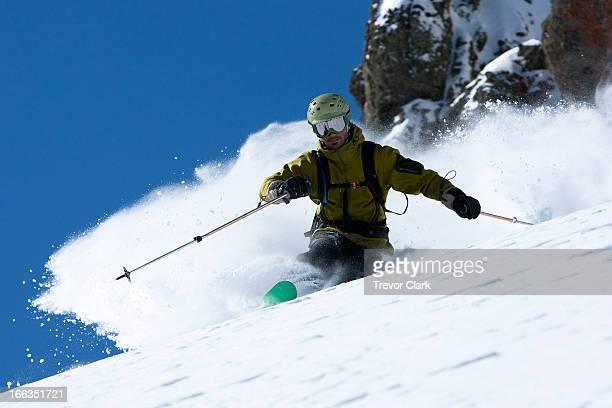 One skier making a hard turn in fresh powder.
