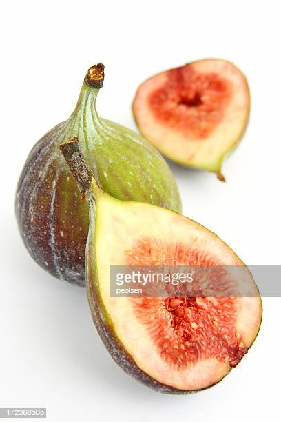 One sliced fig, and one whole fig, on a white background