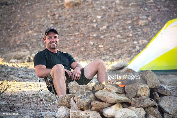 One Smiling Man Sitting by the Campfire