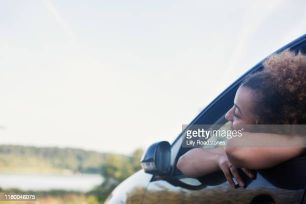 One smiling young woman leaning out of car window