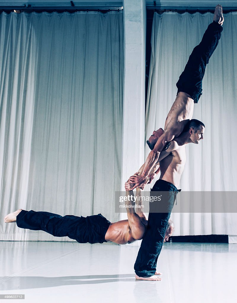 One strong acrobat holds two other men above the ground : Stock Photo