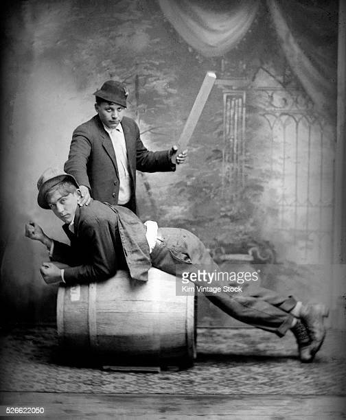 One submissive man leans over a barrel and prepares to be hit by another man with a piece of wood